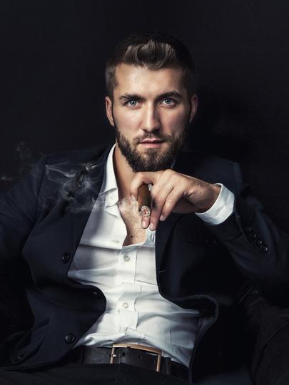 uomo affascinante che fuma il sigaro seduto in poltrona