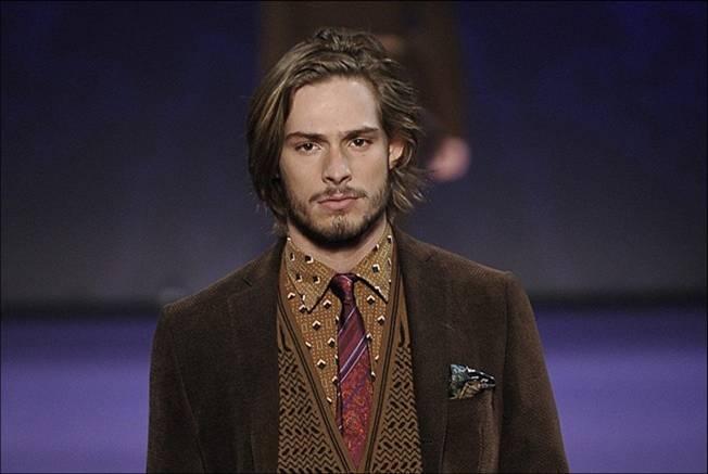 Giovane uomo con giacca di velluto e camicia fantasia colore ocra.