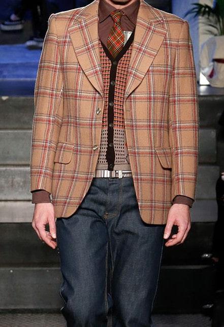 uomo con giacca a quadri e maglioncino fantasia con i jeans