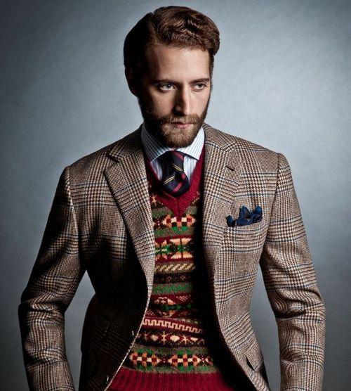 Tomo con barba vestito con giacca principe di galles e maglioncino fantasia